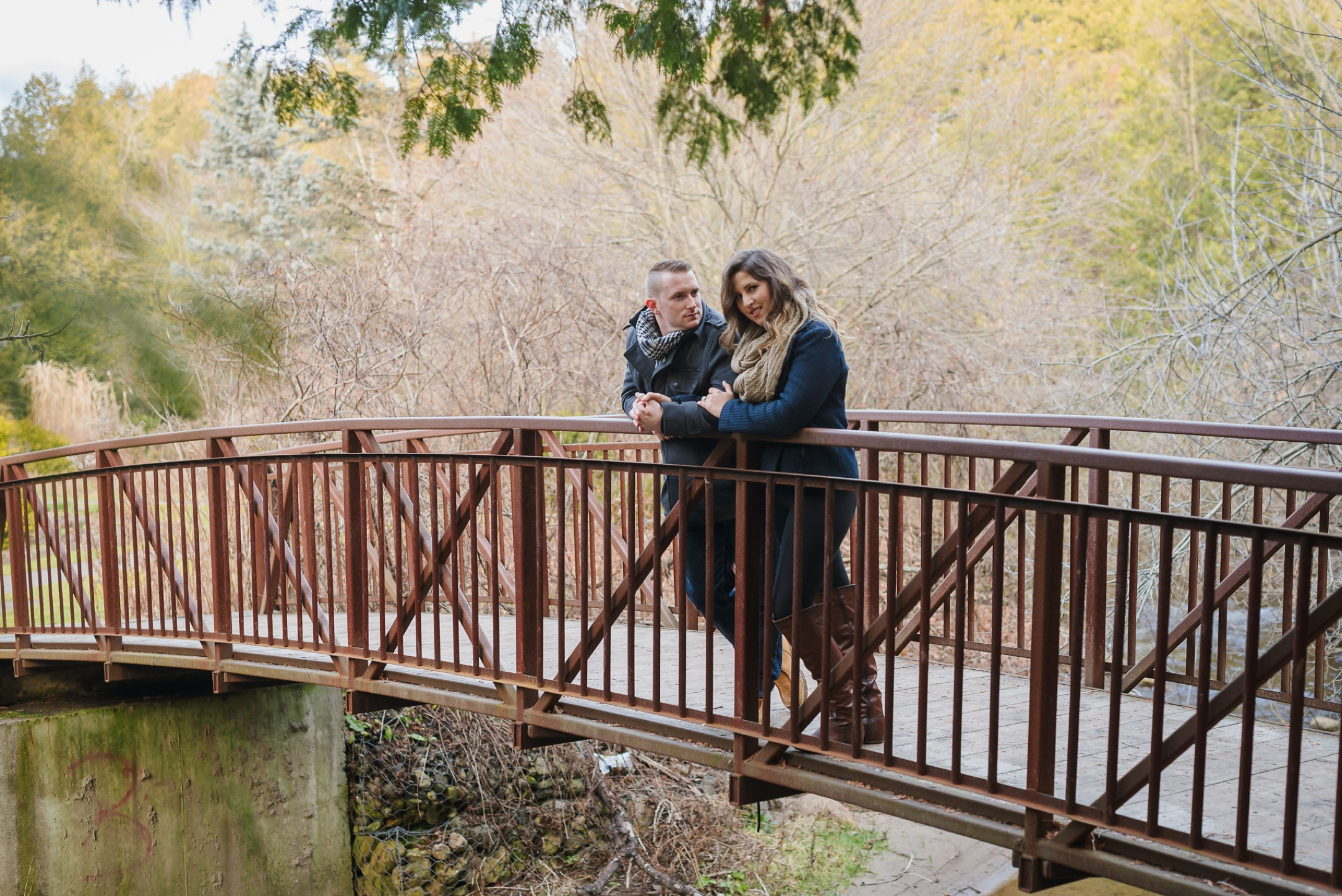 Durham Region, Whitby Engagement Session in the woods, couple sitting on a bridge