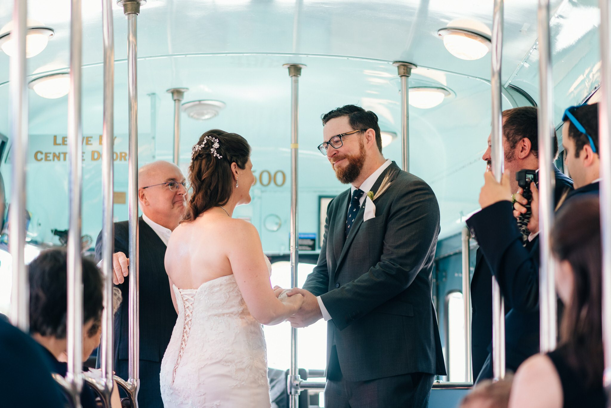 The couple hold hands during their Vintage Toronto Streetcar Wedding