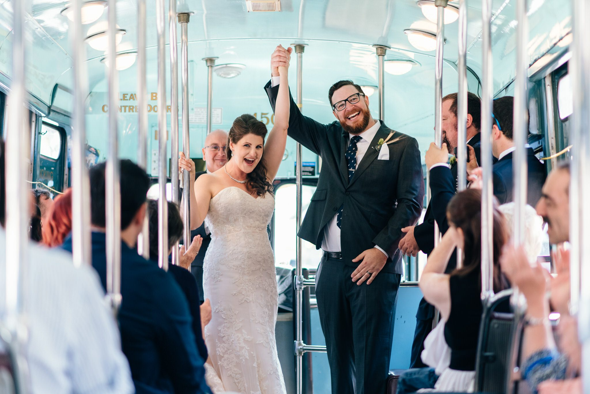 The bride and groom hold their hands in the air in celebration after their Vintage Toronto Streetcar Wedding Ceremony