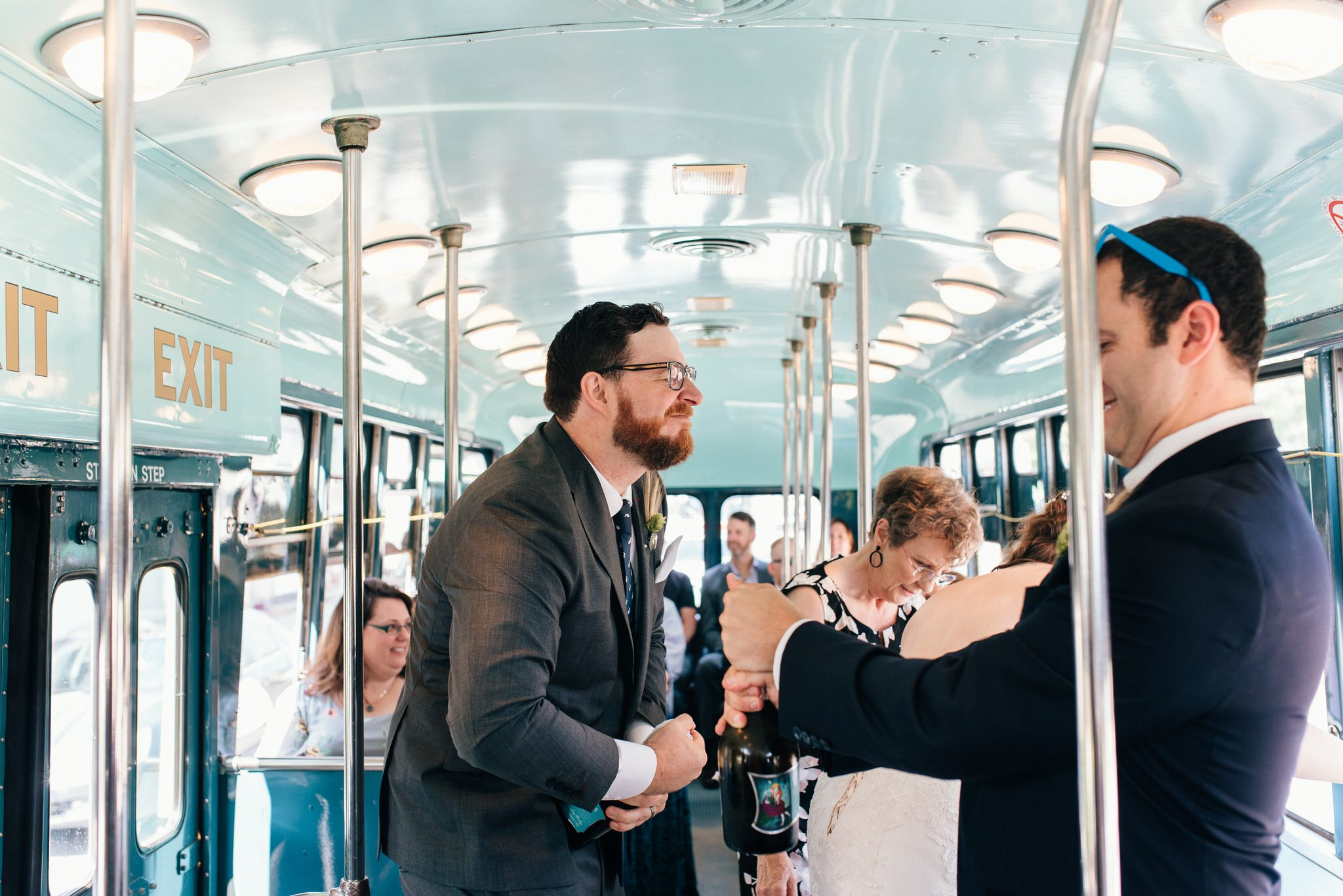 The groom opens a bottle of bubbly to celebrate their Vintage Toronto Streetcar Wedding Ceremony