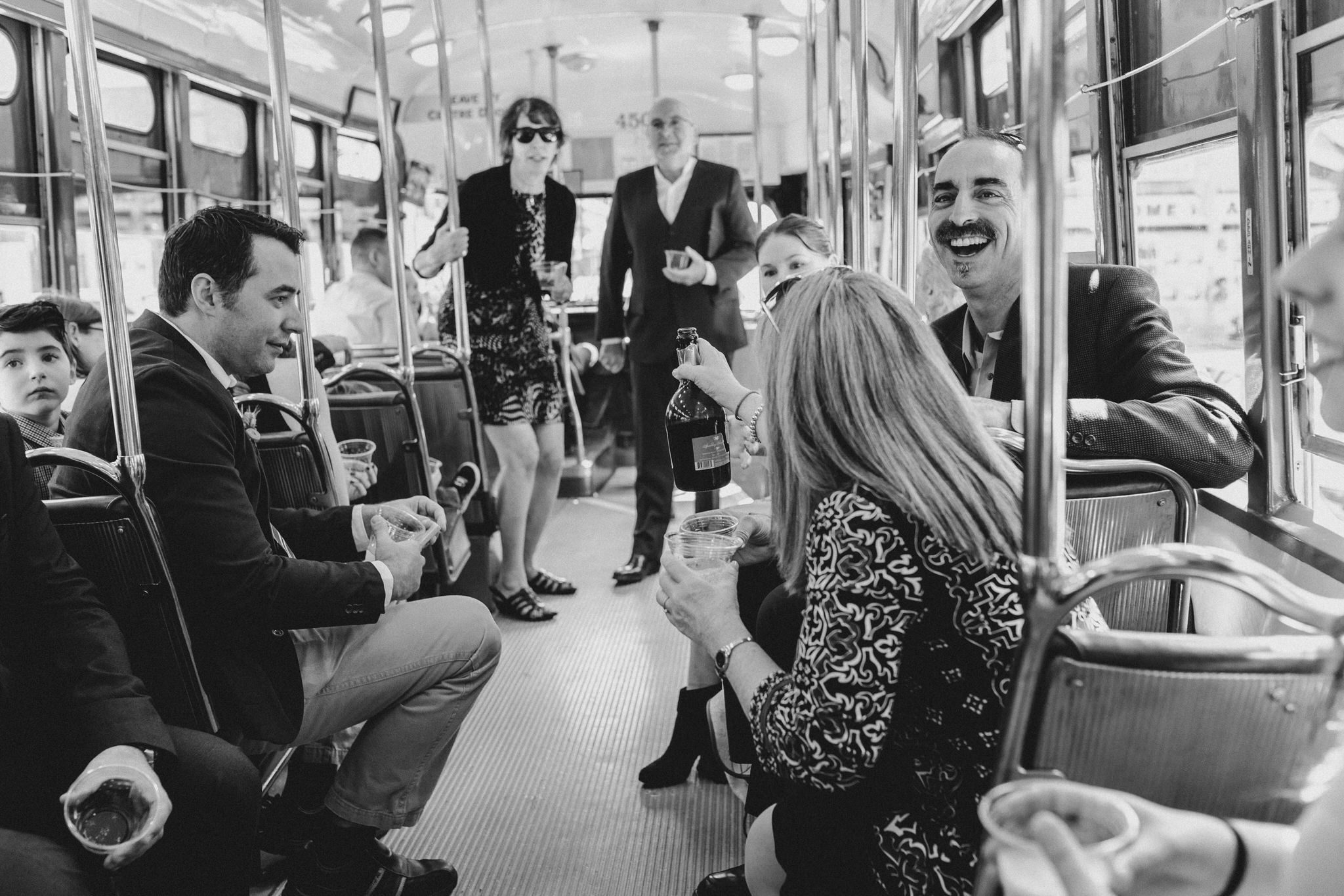 The guests pass around a bottle of bubbly to celebrate their Vintage Toronto Streetcar Wedding Ceremony