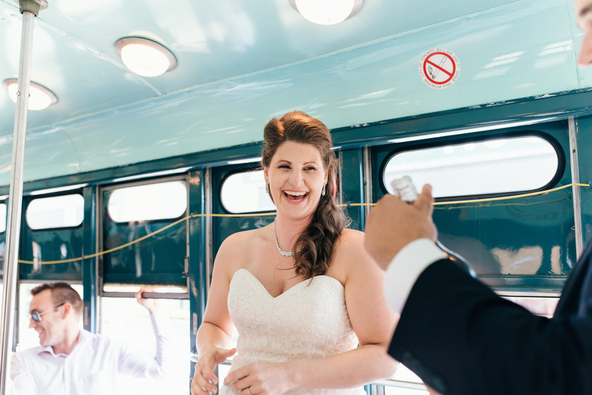 Laughing bride waits for bubbly to celebrate their Vintage Toronto Streetcar Wedding Ceremony