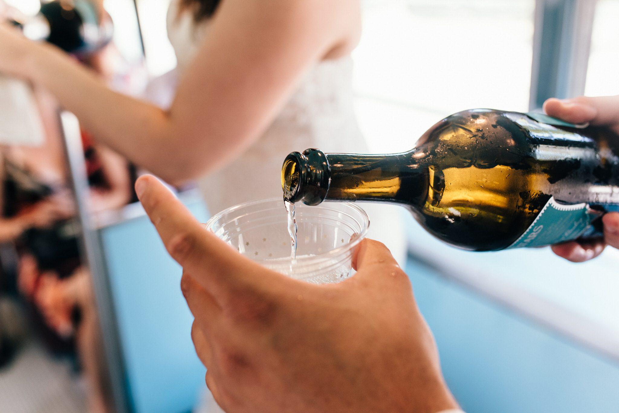 A bottle of bubbly is poured to celebrate their Vintage Toronto Streetcar Wedding Ceremony