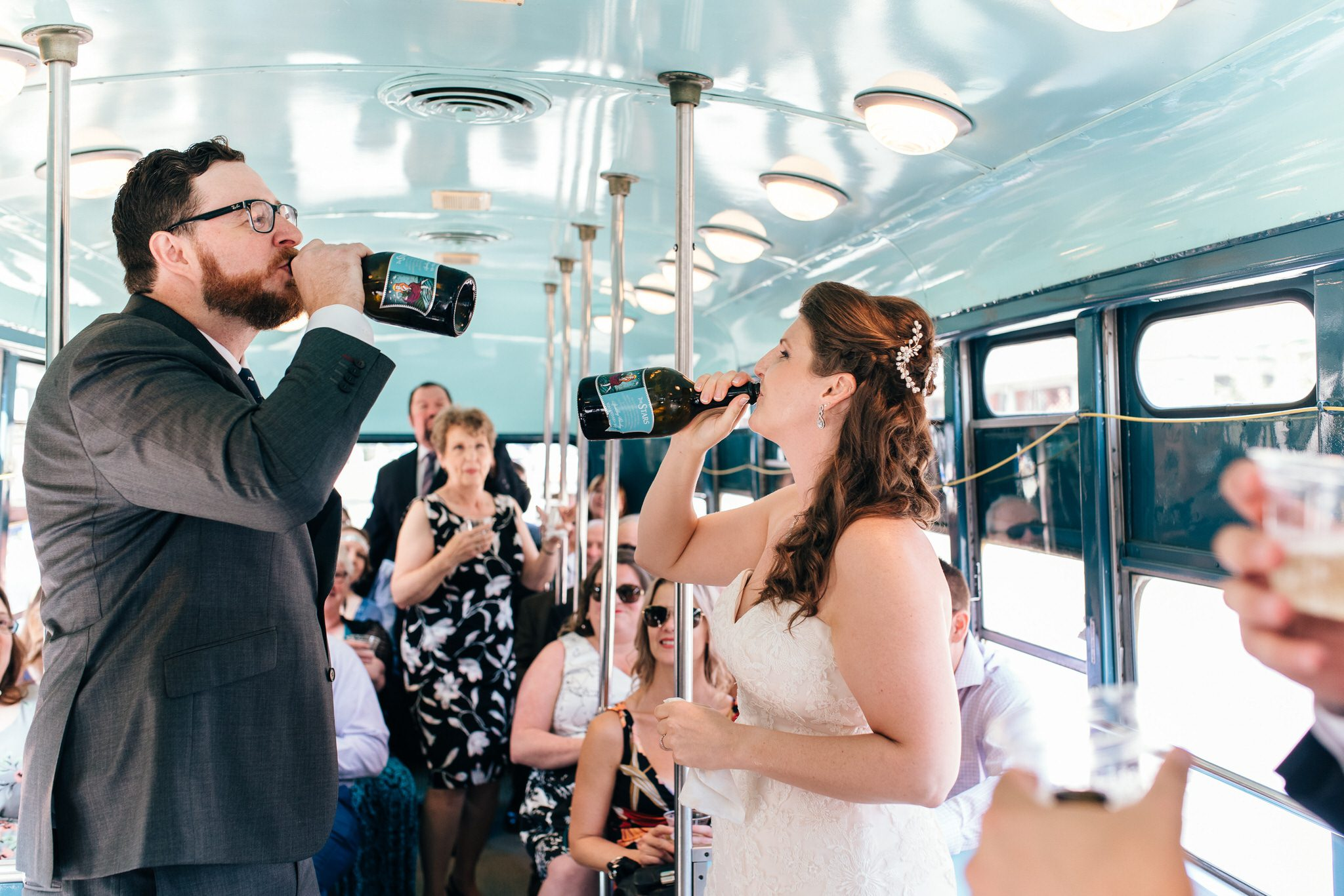 The bride and groom drink from their bottles of bubbly to celebrate their Vintage Toronto Streetcar Wedding Ceremony