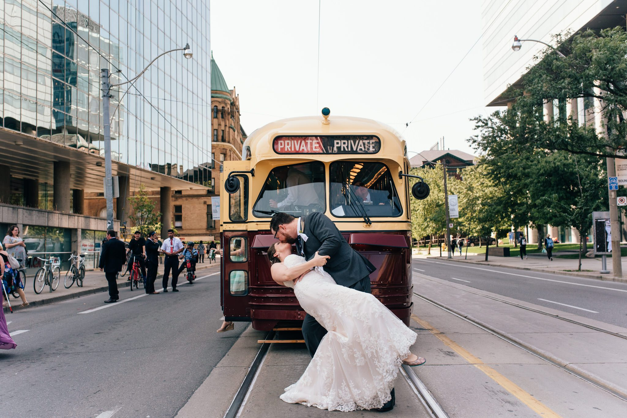 The bride and groom kiss on college street in front of their Vintage Toronto Streetcar Wedding