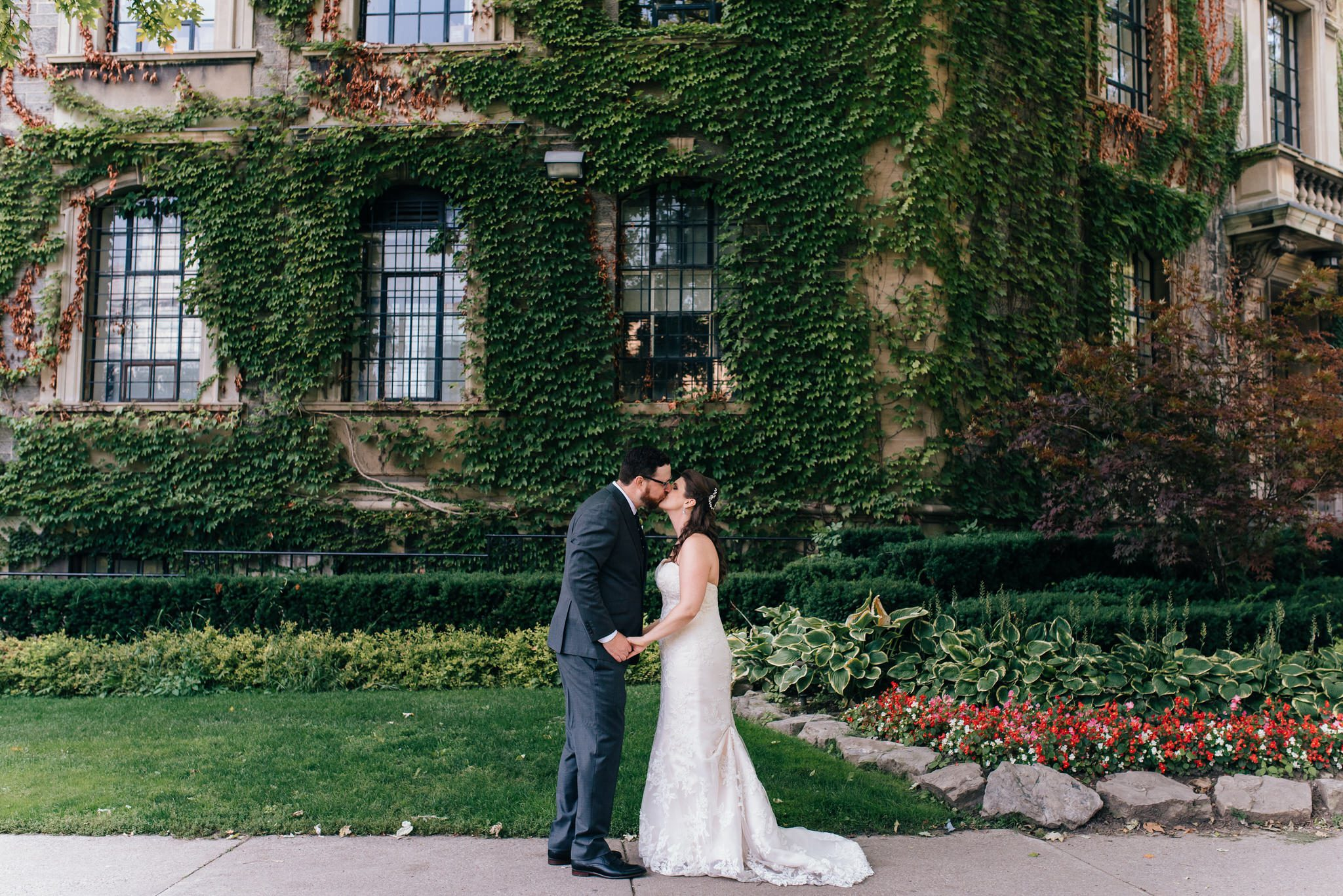The bride and groom kiss in front of an ivy covered University of Toronto building.