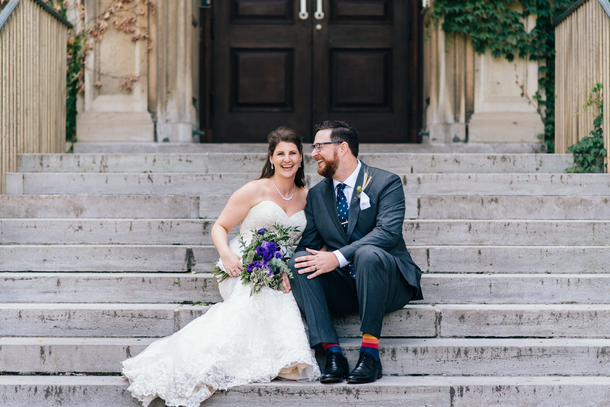 The bride and groom laugh on the steps of an ivy covered University of Toronto building.