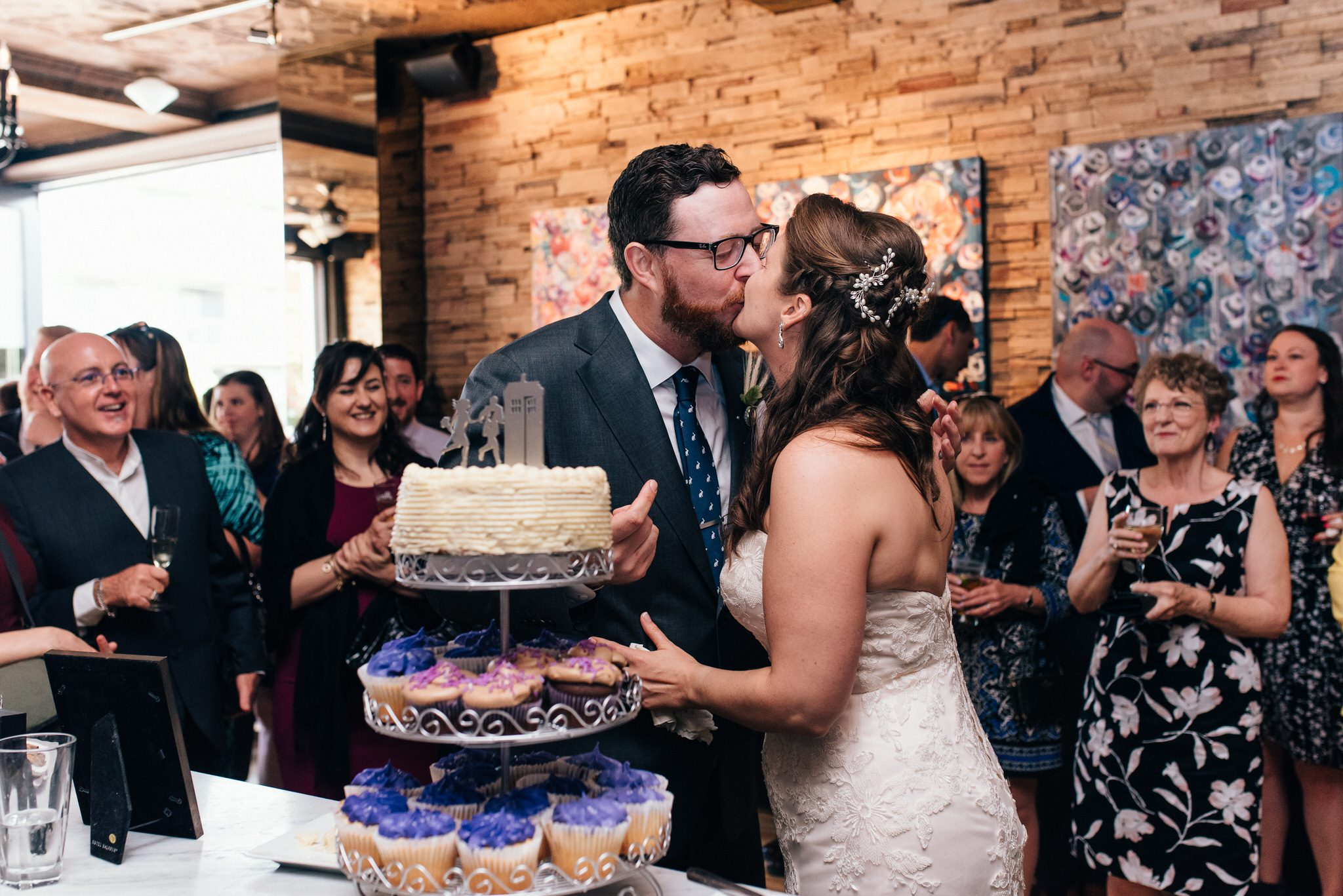 The bride and groom kiss after cutting the cake during their wedding reception at The Rushton Restaurant.