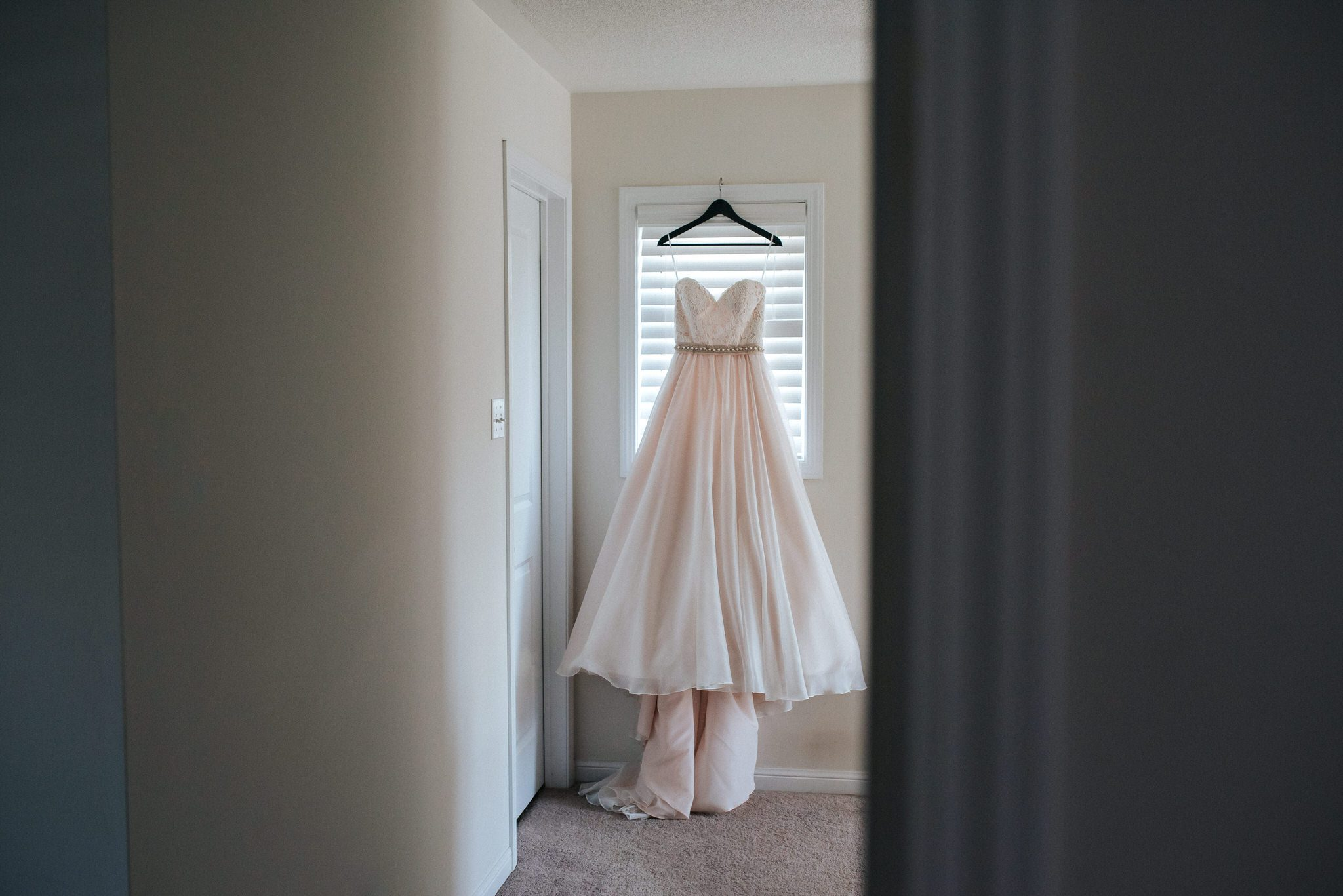 Bloomfield Gardens Wedding - Blush wedding dress hangs in window.