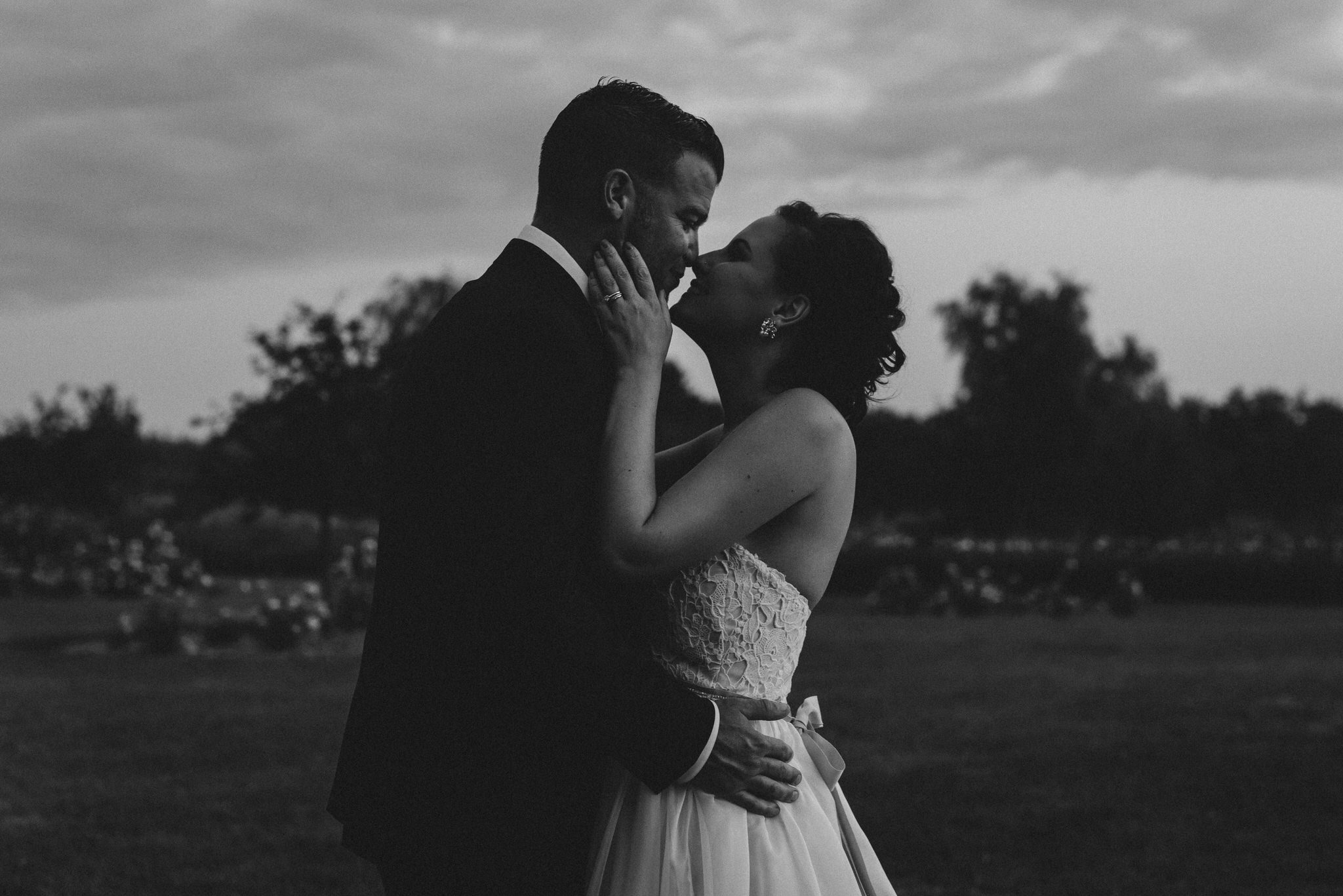 Bloomfield Gardens Wedding - Bride and groom kiss at dusk