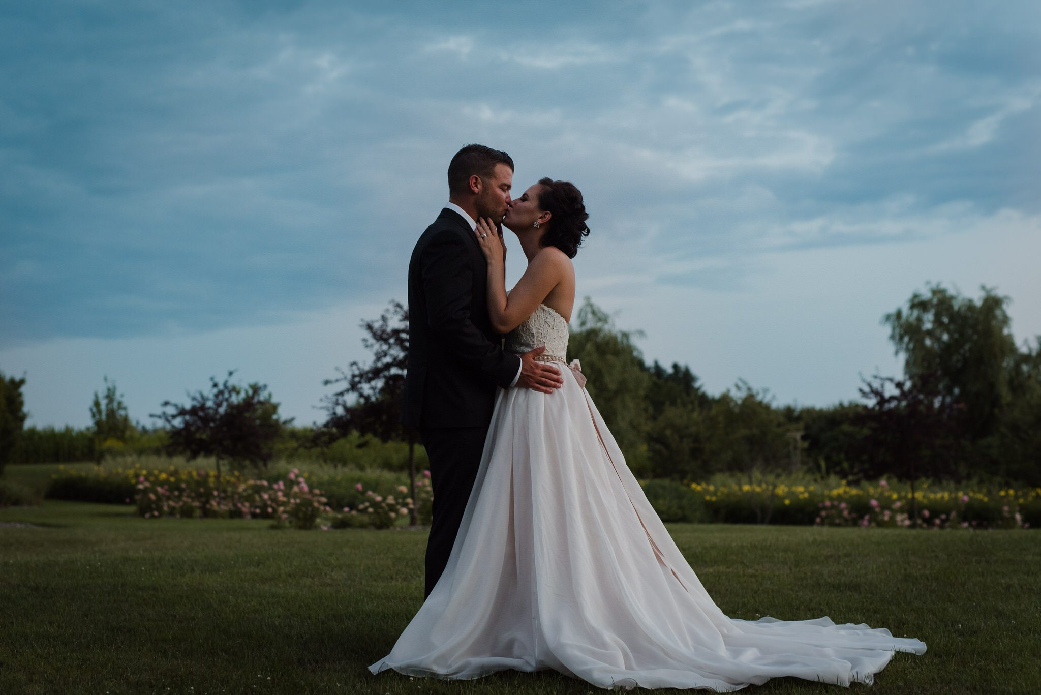 Bloomfield Gardens Wedding - bride and groom kissing at dusk